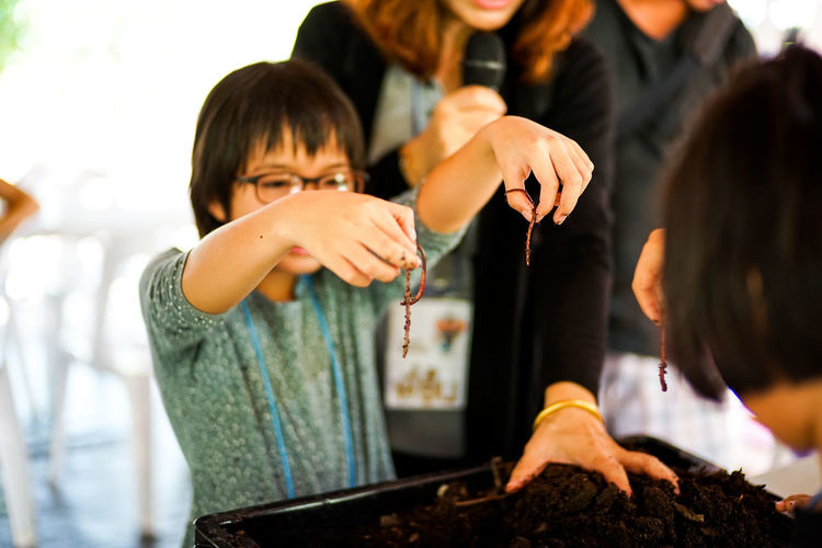 Girl holding earthworms over container