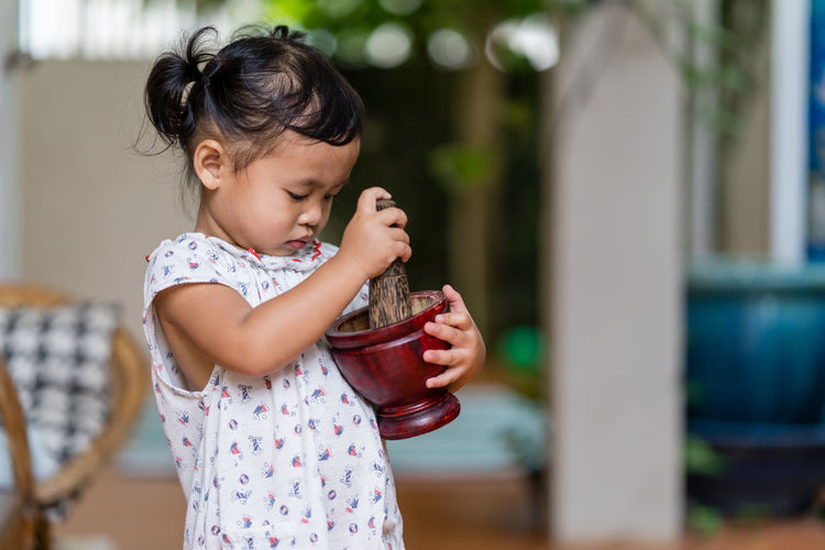 Cute girl holding mortar and pestle at home