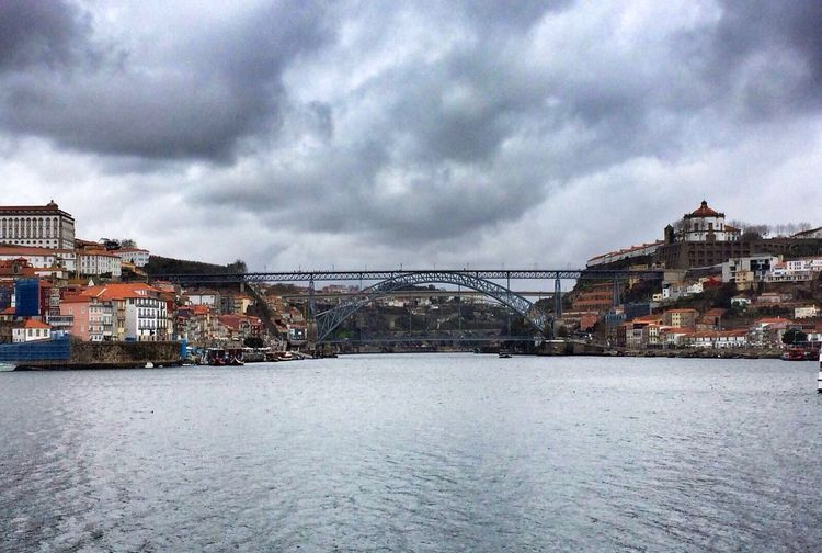 View of bridge over river against cloudy sky