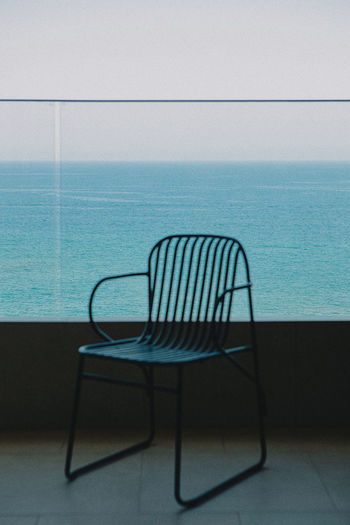 Empty chairs and table against sea against clear sky
