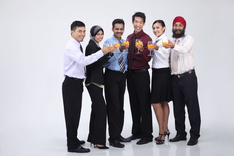 group of people holding glass of orange juice Business Celebration Happiness Indian Teamwork Toast Business Person Chinese Formal Dress  Friendship Front View Full Length Group Of People Harmony Malay Malaysian Mixed Race Multi Racial Orange Juice In Glass Portrait Punjabi Studio Shot Turban United White Background
