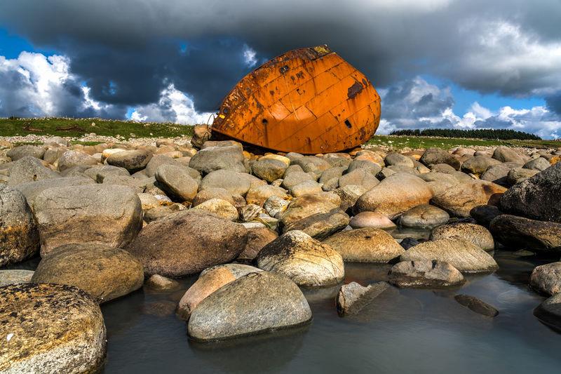 Rocks On Riverbank Against Sky
