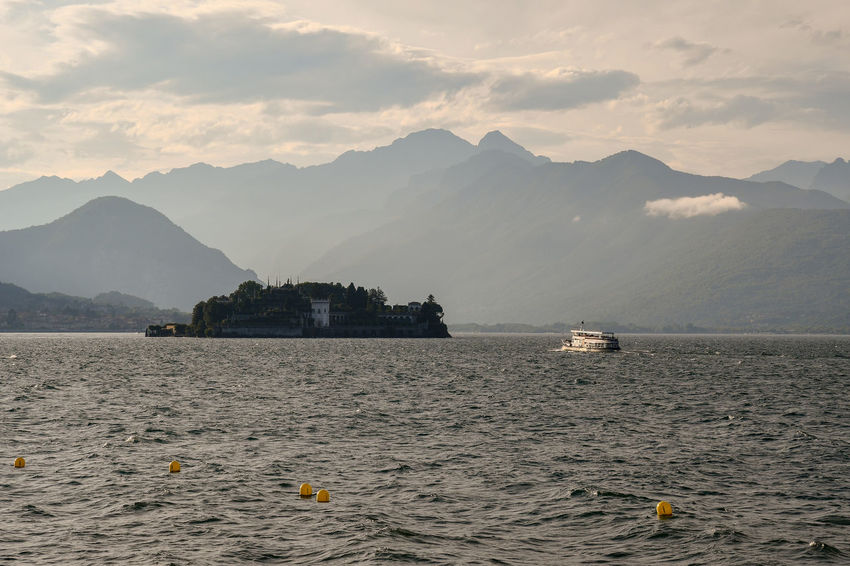 View of Maggiore Lake with Bella Isle and mountainous coast in the background, Piedmont, Italy Mountain Water Mountain Range Scenics - Nature Sky Beauty In Nature Cloud - Sky Nautical Vessel Transportation No People Mode Of Transportation Nature Tranquil Scene Non-urban Scene Tranquility Waterfront Outdoors Ship Boat Lake Isle Isola Bella, Lago Maggiore , Italy Maggiore Lake Piedmont Italy Travel