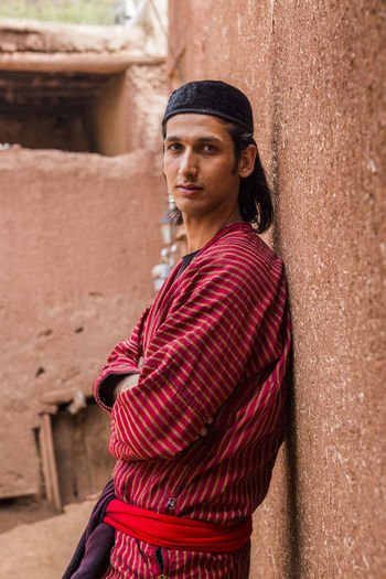 Portrait of man wearing traditional clothes leaning on wall