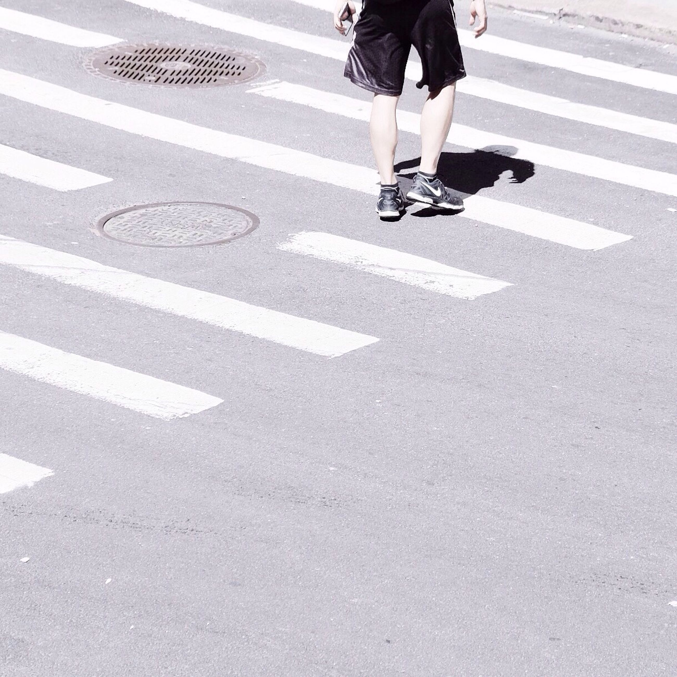 road marking, street, low section, lifestyles, walking, road, zebra crossing, men, person, transportation, leisure activity, city life, shadow, on the move, asphalt, standing, day