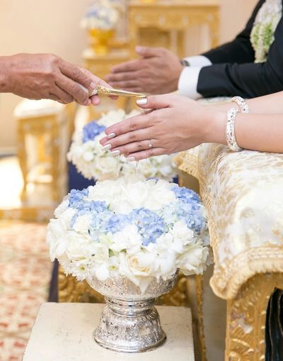 Cropped image of person pouring water on bride hand