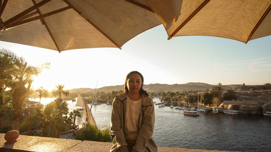 Asian tourist woman at nile river bank sunset in aswan egypt dream exotic trip to africa