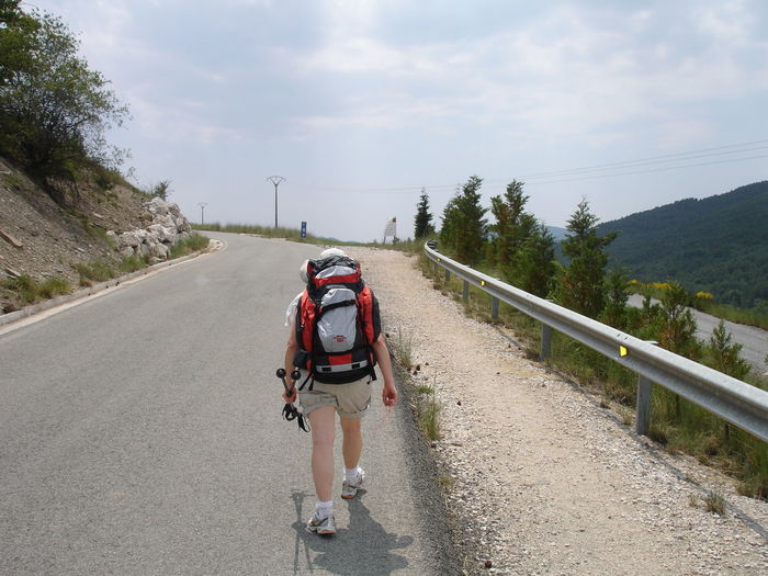Rear View Of A Woman Walking With Backpack On Road