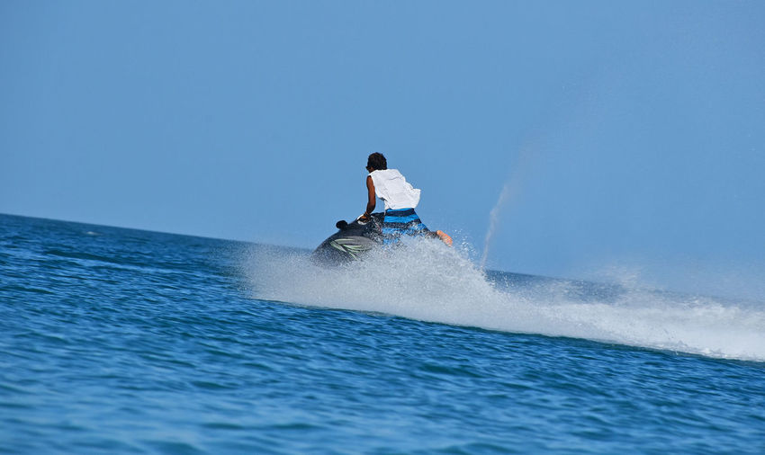 Rear view of man on jet boat over sea against clear sky