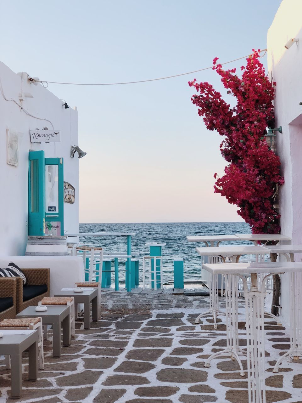 CHAIRS AND TABLE BY SEA AGAINST BUILDINGS
