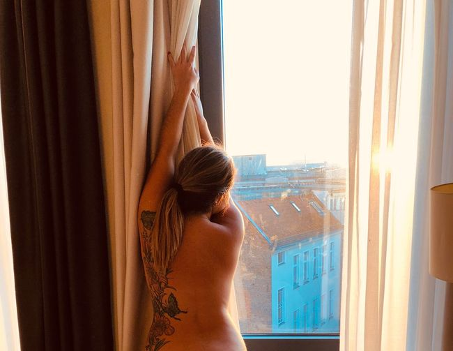 Rear view of sensuous naked woman looking through window
