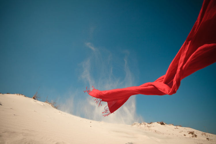 Red scarf waving over sand against blue sky
