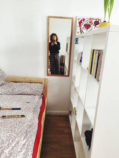 Reflection Of Woman Photographing On Mirror At Home