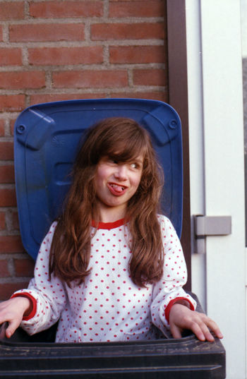 Playful Girl Sticking Out Tongue While Standing In Garbage Bin