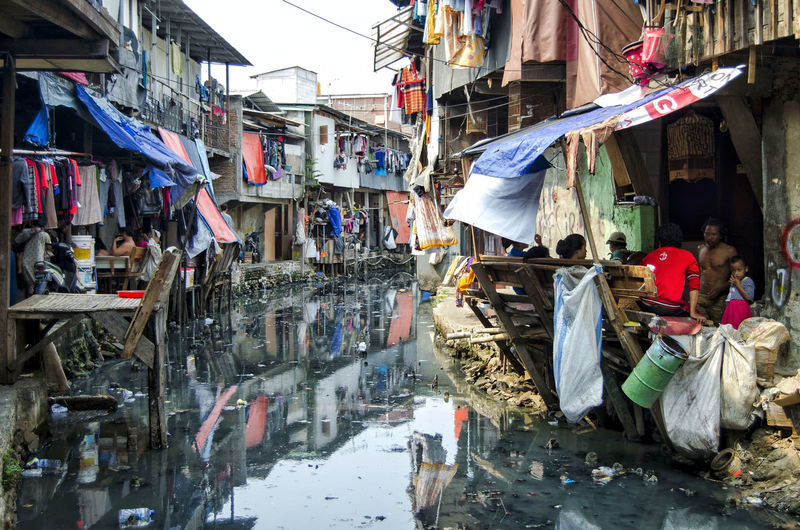 slum Home Jakarta Abundance Architecture Building Building Exterior Built Structure Choice City Clothing Day Hanging Incidental People Jakarta Indonesia Large Group Of Objects Market Messy Outdoors Residential District Retail  Slum Street Street Market Variation Water