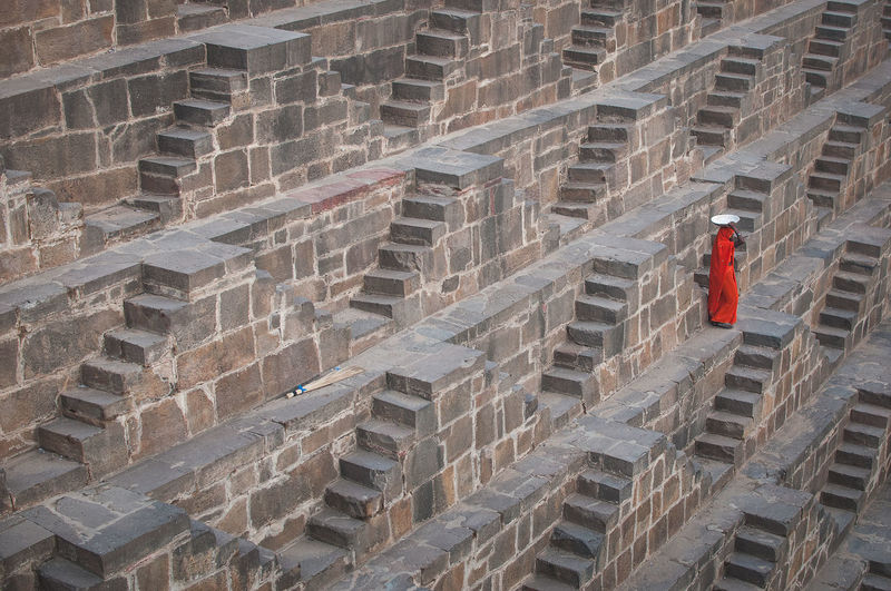 A shot of an Indian female going down lots of stairs at Chand Baori Step Well in India just to get some water. 2016 Baswa Indian Stairs Adult Architecture Built Structure Chand Boari Day Editorial Use Only Full Length Geometry Indoors  Lifestyles One Person Outdoors People Real People Red