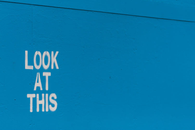 Close-up of text on blue wall