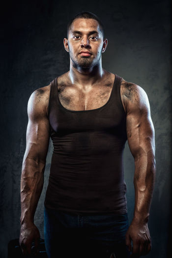 Portrait of confident muscular worker standing against wall