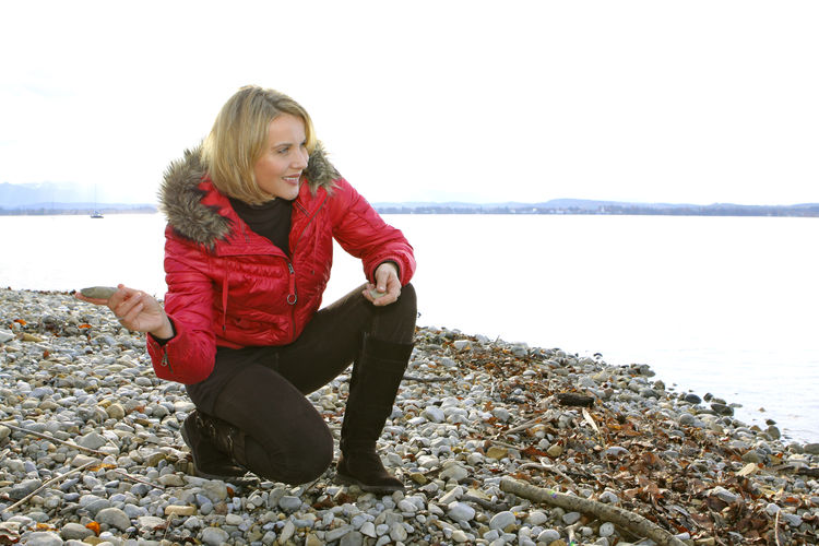 Blonde middle-aged woman on an autumn walk at the lake, portrait Autumn Walk Beach Beautiful Woman Blond Hair Casual Clothing Front View Full Length Lake Lakeside Leisure Leisure Activity Lifestyles Middle Aged One Person Outdoors Pebble People Real People Sea Sitting Water Women Young Adult Young Women