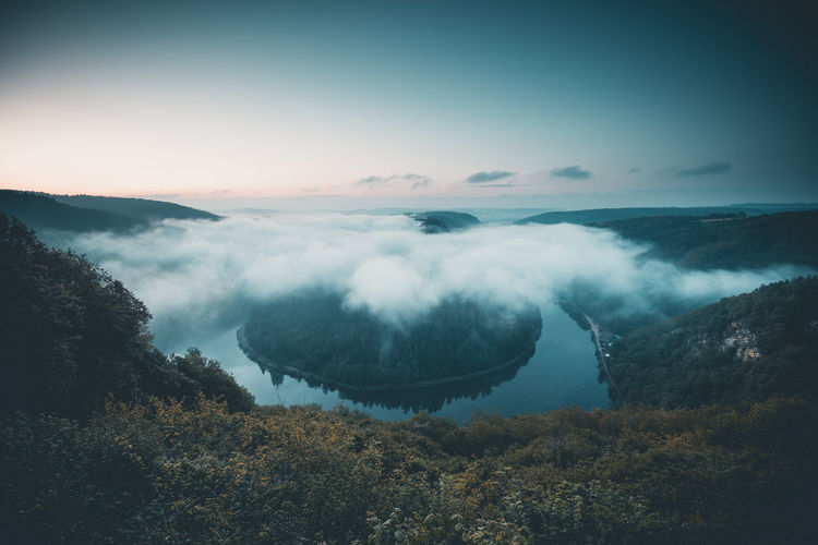 Bow if river Saar in Germany close to Orscholz before sunrise. Germany Saarschleife Scenics - Nature Beauty In Nature Sky Tranquil Scene Tranquility Mountain Cloud - Sky Nature No People Environment Non-urban Scene Tree Idyllic Landscape Day Outdoors Fog Moody Clouds Cloud And Sky This Week On Eyeem Morning Morning Light Morning Sky Landscape_Collection Plant Water River