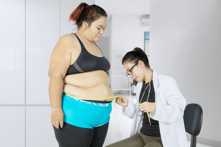 Doctor examining overweight patient at hospital