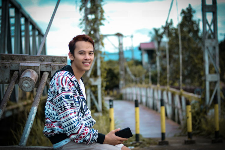 Portrait of smiling young man holding mobile phone sitting outdoors