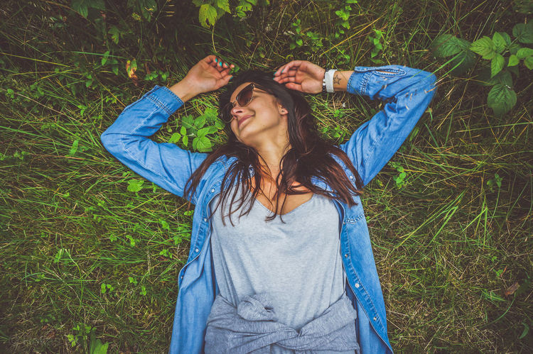 Beautiful Woman Blue Casual Clothing Day Denim Jacket Field Front View Grass Hands Behind Head Happiness High Angle View Leisure Activity Lifestyles Live For The Story Lying Down Lying On Back Nature One Person One Woman Only One Young Woman Only Outdoors Real People Smiling Young Adult Young Women
