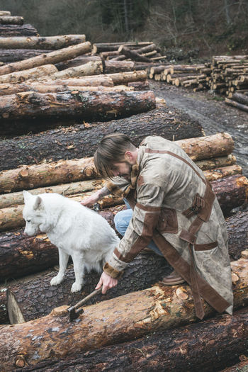 High angle view of young man with dog chopping wood in forest