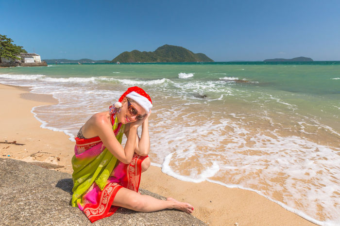 Beautiful, fashionable woman with red Santa Claus hat relaxing and catching tan on rocks of a tropical beach for xmas holiday in Laem Ka Beach, Phuket, Thailand. Blonde Christmas Greeting Happy Hat Lady M MOVIE Merry Christmas! NYE New Year Red Santa Santa Claus Woman Beach Beauty In Nature Claus Day Decoration Gift Greeting Card  Leisure Activity Lifestyles Model Nature One Person Outdoors Present Real People Sand Sea Smilig Water Young Adult Young Women