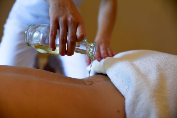 Midsection Of Woman Pouring Essential Oil On Customer Back At Spa
