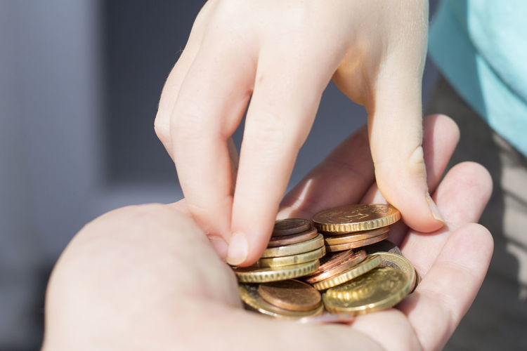 Cropped hand of woman giving coins to friend