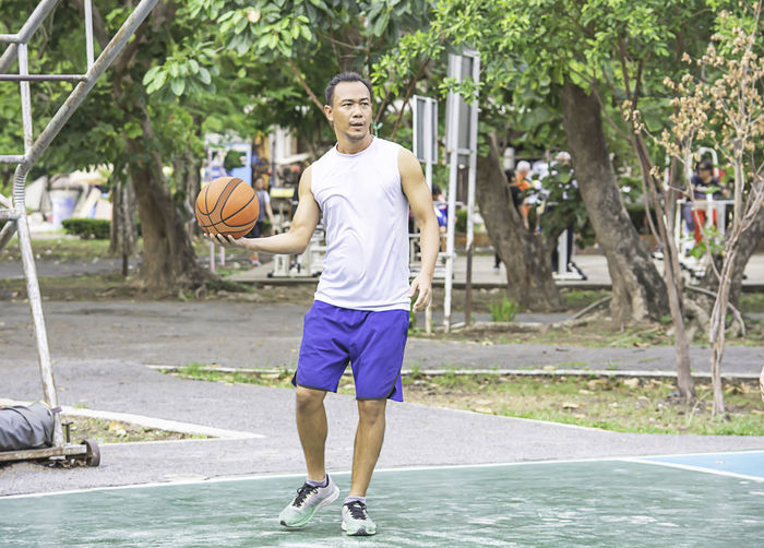 Basketball in hand Asian man to exercise Background tree at Bang Yai Park , Nonthaburi in Thailand. Health Portrait Male Outside Smile Park Beautiful Happy Active Activity Adult Agility Athlete Background Ball Basketball Body Caucasian Effort Equipment Exercise Fitness Fun Game Garden Goal Healthy Holding Hoop Jump Leisure Man Men Motion Nature Outdoor Outdoors People person Play Score Slam Sport Sports Sportsman Strong Throw Throwing  Tree White