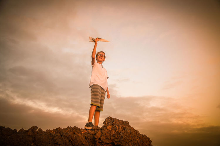 Low angle view of boy holding paper airplane against sky during sunset