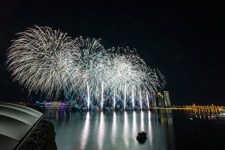 Reflection of firework display on river against sky