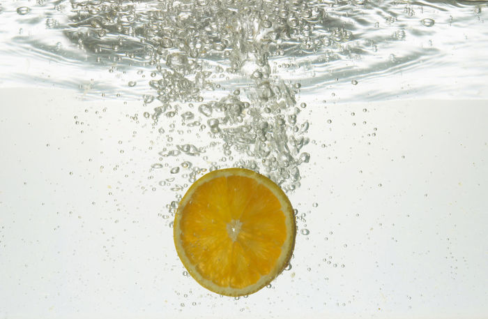 dropping of orange slice into water Air Bubbles Bubbles Falling Orange Slice Action Close-up Drink Drop Dropping Water Food Food And Drink Fresh Freshness Healthy Eating No People Orange - Fruit Sliced Fruit Slices Water