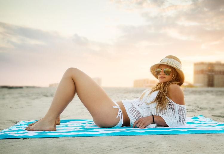 Full length of woman relaxing at beach
