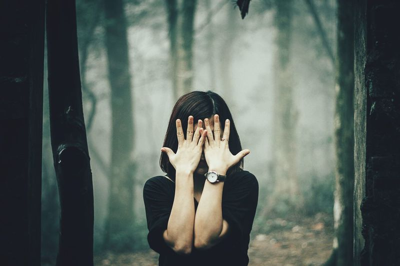 Woman covering face with hands while standing against trees