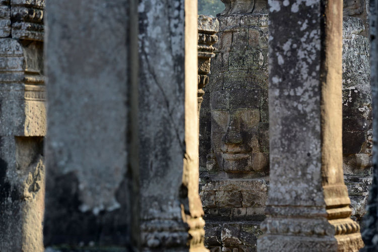 Columns against buddha head carved on bayon temple