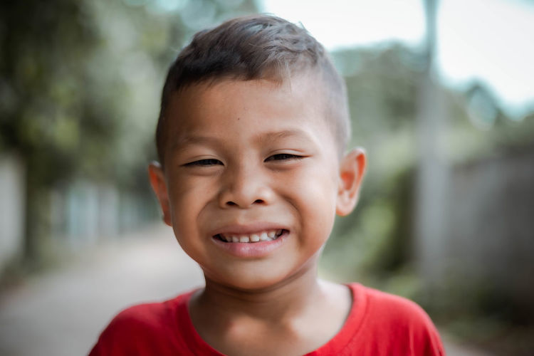 Close-up portrait of smiling boy standing outdoors
