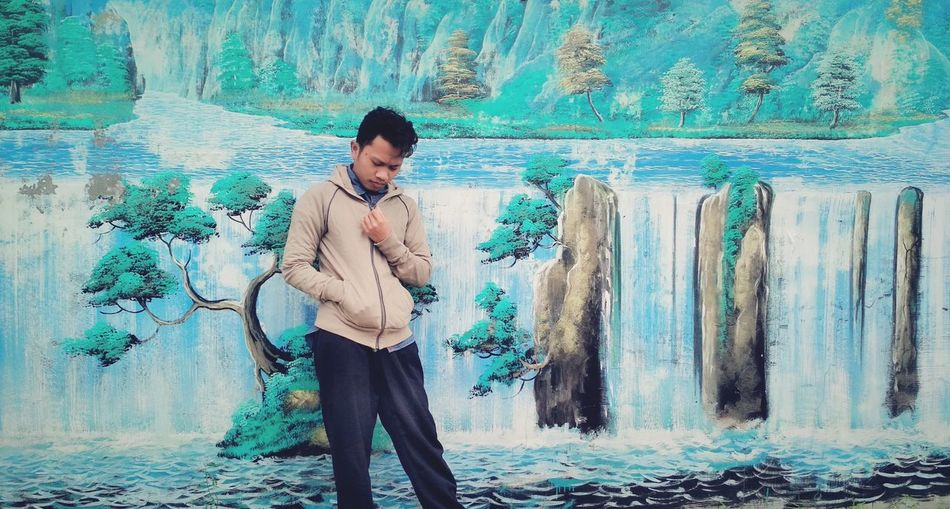 Young man standing against mural on wall