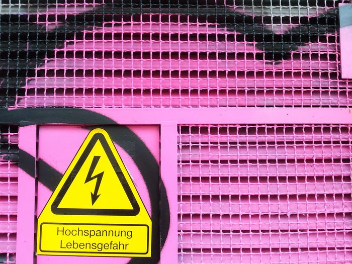 High voltage sign on metallic wall