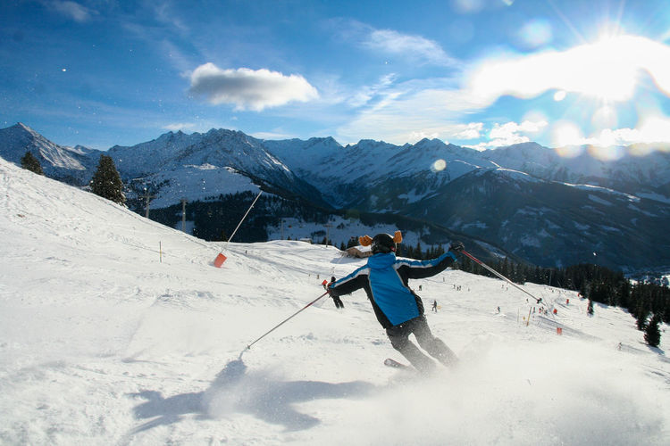 Rear view of person skiing on mountain against sky