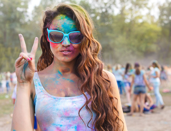 Girl showing peace sign while playing holi