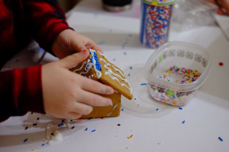 Cropped hand making gingerbread house on table