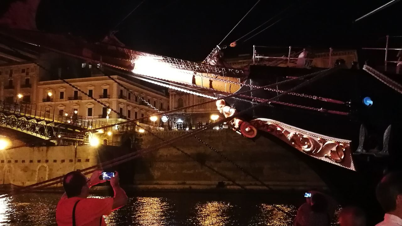 night, illuminated, transportation, real people, mode of transport, men, built structure, lifestyles, one person, architecture, bridge - man made structure, nautical vessel, outdoors, water, women, human body part, human hand, city, sky, people
