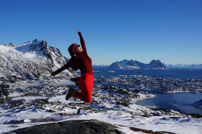 Full Length Of Woman Jumping On Snow Covered Mountain