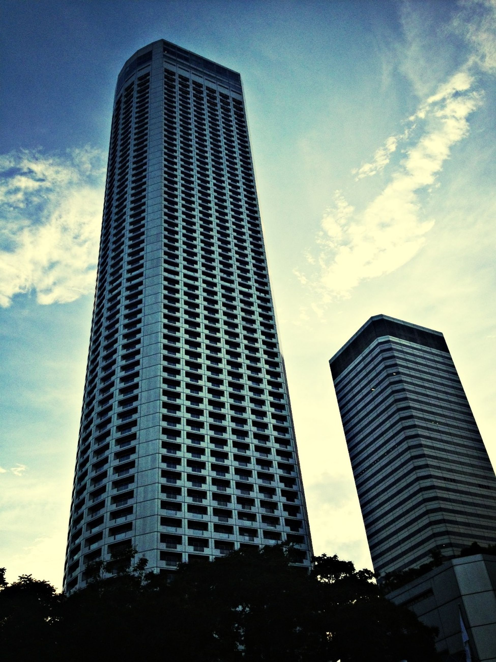 architecture, building exterior, low angle view, built structure, skyscraper, tall - high, modern, sky, office building, city, tower, cloud - sky, glass - material, tall, cloud, building, day, no people, reflection, outdoors