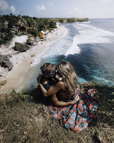 High angle view of couple embracing while sitting on rock against sea