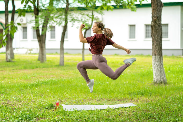 Full length of young woman jumping in field