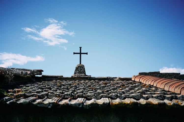 Cross on church roof against sky